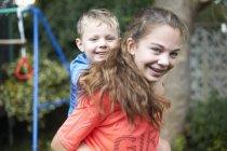 Портрет молодої дівчини, що несе молодого брата на спині — стокове фото