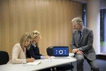 Colegas usando laptop na sala de conferências — Fotografia de Stock