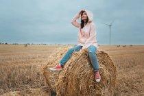 Woman in raincoat on hay bale, Odessa, Ukraine — Stock Photo