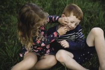 Niño y hermana jugar a la lucha en el campo - foto de stock