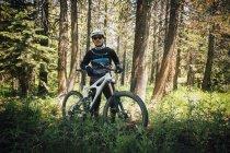 Человек в лесу с горным велосипедом, глядя в камеру, озеро Маммот, Калифорния, США, Северная Америка — стоковое фото