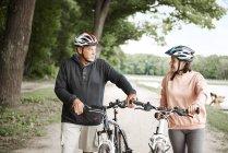 Зрелая пара, идущая по сельской дороге на велосипедах — стоковое фото