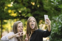 Two young female friends pulling faces for smartphone selfie in park — Stock Photo
