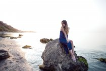 Young woman sitting on beach rock — Stock Photo
