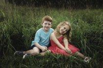 Портрет девушки и брата, сидящих в поле — стоковое фото