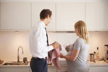 Pregnant couple in kitchen looking at cook book — Stock Photo