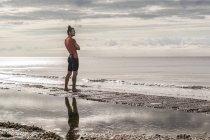 Uomo sulla battigia che guarda lontano la vista del mare — Foto stock