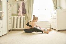 Vista lateral de la mujer embarazada y su hija en el dormitorio - foto de stock