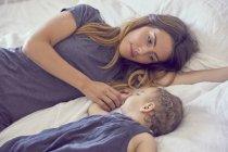 Мати і дочка, лежачи на ліжку разом — стокове фото