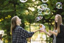 Два молодих подруг робить плаваючим бульбашки в парку — стокове фото