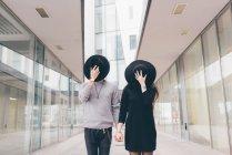 Retrato de jovem casal em ambiente urbano, de mãos dadas, cobrindo rostos com chapéus — Fotografia de Stock