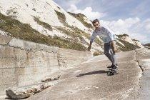 Jeune skateboard masculin près du mur de la mer — Photo de stock