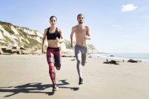 Giovane uomo e donna che corrono lungo la spiaggia — Foto stock