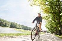 Старший человек велоспорт на пути у озера — стоковое фото