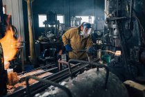 Blacksmith shaping red hot metal rod in workshop — Stock Photo