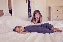 Femme tout-petit, dormant sur le lit, soeur aînée regardant son sommeil — Photo de stock