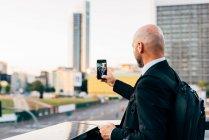 Зрелый бизнесмен делает селфи на открытом воздухе — стоковое фото