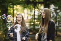 Два молодих подруг тріщить плаваючим бульбашки в парку — стокове фото