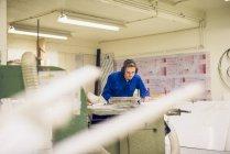 Ouvrier d'usine portant des vêtements de protection, travaillant sur la machine de fabrication — Photo de stock