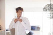Homme dans le salon boutonnage chemise — Photo de stock
