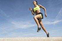 Низкий угол обзора молодой женщины, бегущей против голубого неба — стоковое фото