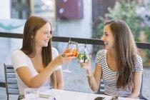 Due giovani amici femminili alzando un brindisi cocktail at sidewalk cafe — Foto stock