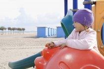 Fille sur l'équipement de terrain de jeu sur la plage regardant loin — Photo de stock