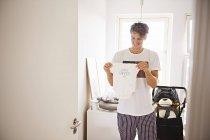 Homem no berçário segurando a roupa do bebê — Fotografia de Stock