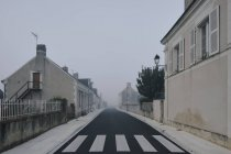 Empty road through Meigne-le-Vicomte village on misty morning, Loire Valley, France — Stock Photo