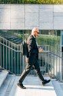 Mature businessman walking outdoors, using smartphone — Stock Photo