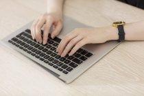 Mujer escribiendo en el teclado del ordenador portátil - foto de stock