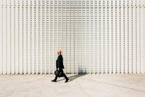 Homme d'affaires mature marchant à l'extérieur, portant un casque de moto, vue latérale — Photo de stock
