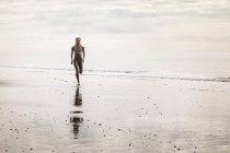 Jovem mulher correndo ao longo praia — Fotografia de Stock