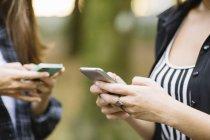 Foto ritagliata di due giovani donne che utilizzano il touchscreen dello smartphone nel parco — Foto stock