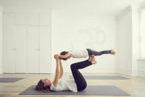 Mother and daughter in yoga studio, daughter balancing on mothers legs — Stockfoto