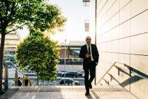 Homme d'affaires mature tenant smartphone en plein air — Photo de stock