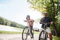 Зрелая пара смеется и катается на велосипеде у озера — стоковое фото