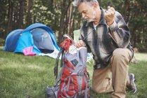 Старший чоловік біля намету пакування рюкзака — стокове фото