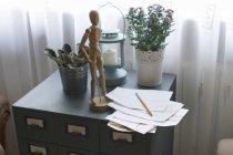 Maniquí de madera de la artista en archivador, con lápiz y papel - foto de stock