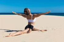 Rear view of woman on beach in yoga position — Stock Photo