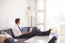 Businessman using laptop on sofa in living room — Stock Photo