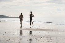 Visão traseira de jovens homens e mulheres correndo descalços ao longo da praia — Fotografia de Stock