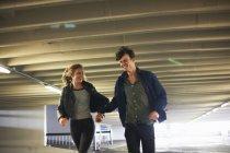 Молодая пара смеется, когда бежит через подземный ход — стоковое фото
