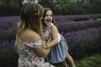Mother and daughter playing in lavender field — Stock Photo