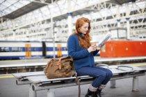 Woman on bench at train station platform — Stock Photo