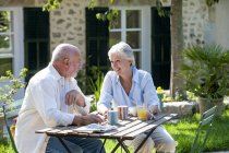 Senior couple sitting in garden, coffee cups on table — Stock Photo
