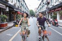 Couple de hipster ethniques multi vélo le long de la ville, rue, Concession Français de Shanghai, Shanghai, Chine — Photo de stock