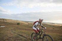 Mountain biker riding up on moorland track — Stockfoto
