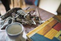Dettaglio del dipinto su tela e pennelli sul tavolo di studio di artisti — Foto stock