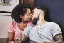 Multi ethnic hipster couple in cafe kissing, Shanghai French Concession, Shanghai, China — Stock Photo
